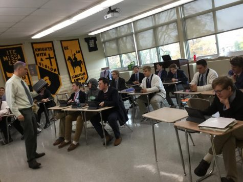 Mr. Hoelperl of the Theology Department teaches a lesson to one of his junior classes using the iPads.