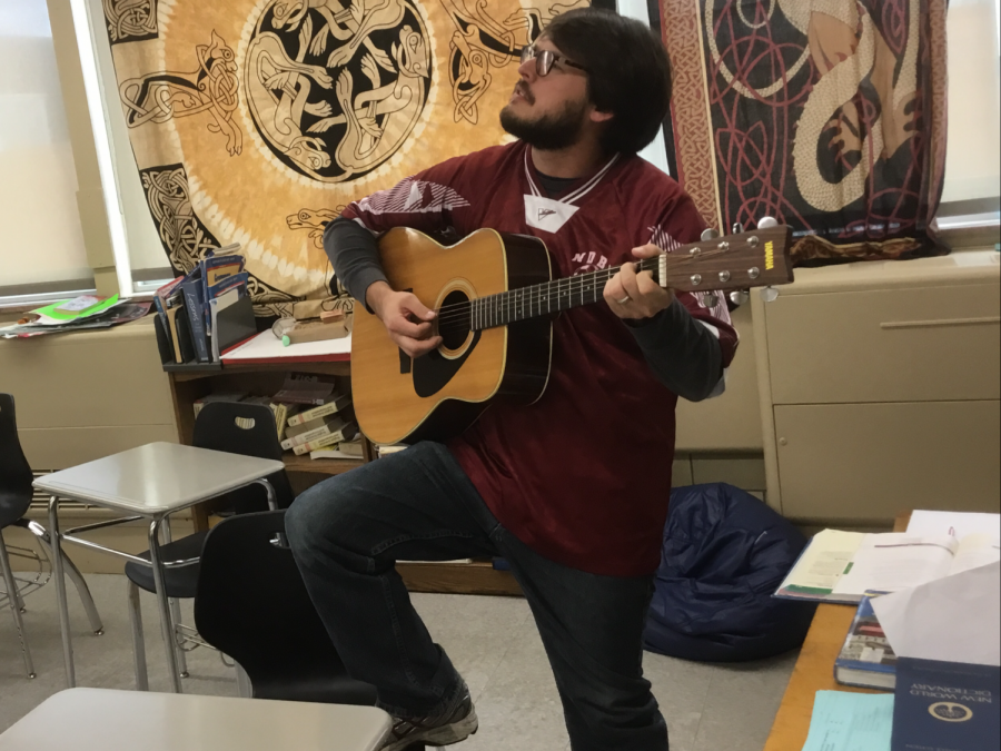 Mr.+Anthony+Lessard+gazes+into+the+distance+strumming+his+six+string+in+his+classroom+on+Thursday%2C+October+18.+Mr.+Lessard+is+a+notable+advocate+for+a+greater+number+of+music+clubs+at+McQuaid.+