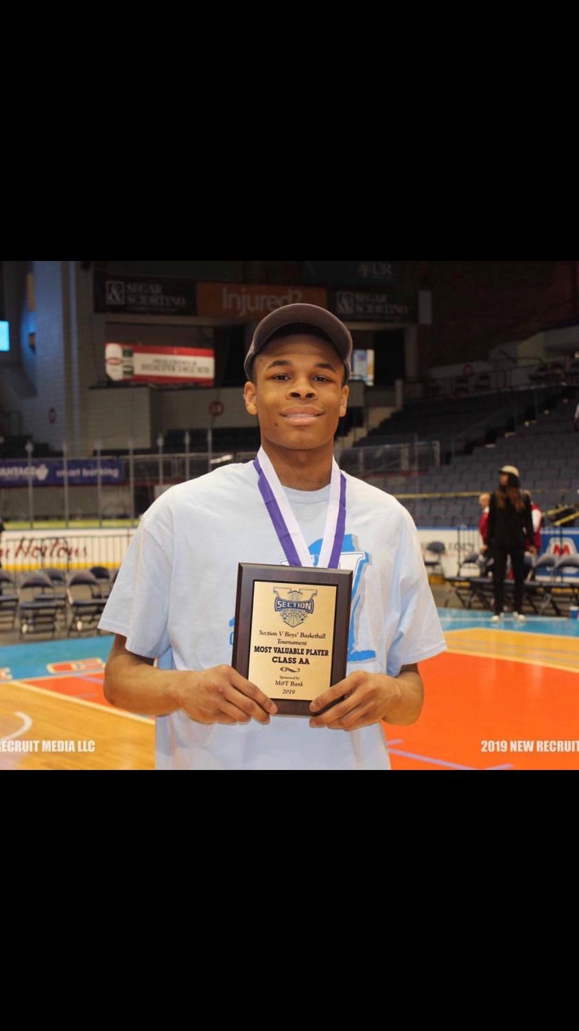Junior guard Jermaine Taggart holds MVP award after championship game in Blue Cross Arena.
