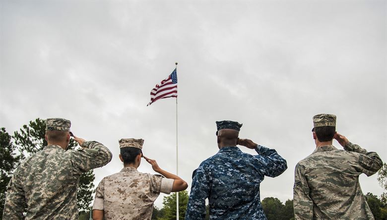 Servicemen+and+women+of+various+branches+salute+our+flag.