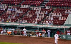 Boston Redsox player walks back to dugout as cardboard fans look on. These cut outs have replaced many of the fans in stadiums now.